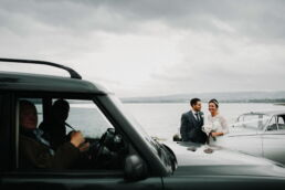 bride and groom being photo bombed by car