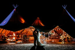 night photograph of bride and groom outside tipi