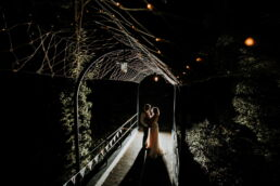 bride and groom under festoon lighting