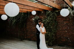 bride and groom stood under decorations outside