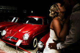 bride and groom kissing in the Haynes motor museum