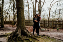 couple cuddling in park in London engagement photoshoot