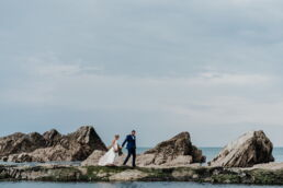 groom leading bride along the edge of tidal pool