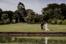 reflection of the bride and groom in lake at pennard house