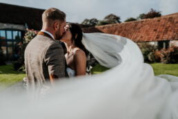 wedding veil with the bride and groom kissing