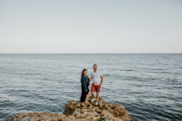 couple stood on rocks on beer beach during engagement photoshoot