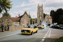 bride and groom leaving church wedding in drift cars