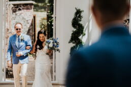bride and dad walking down the aisle in the orangery