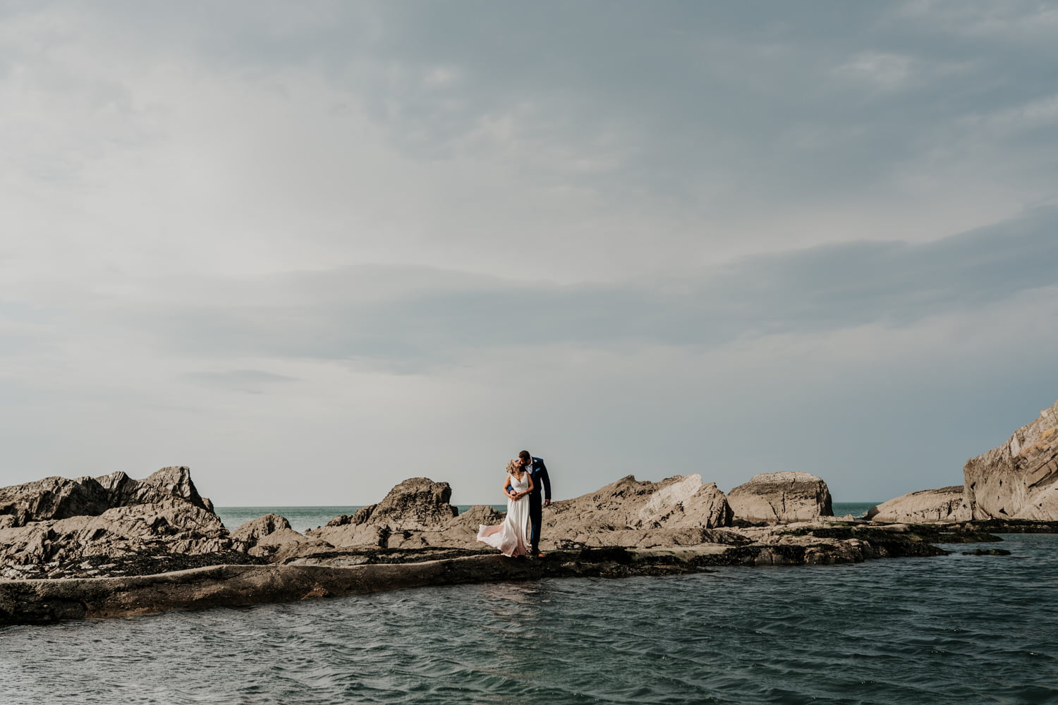 bride and groom on edge of tidal pool
