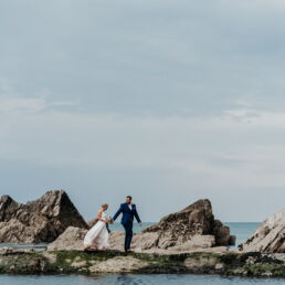 bride and groom on the tidal pool at tunnels beaches