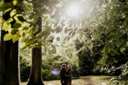 couple stood under trees for engagement photoshoot