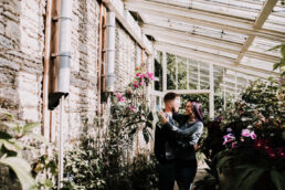 couple cuddling in the greenhouse at lacock