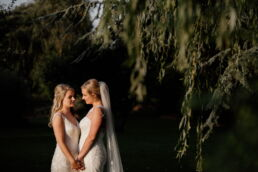 brides stood together in gardens during wedding