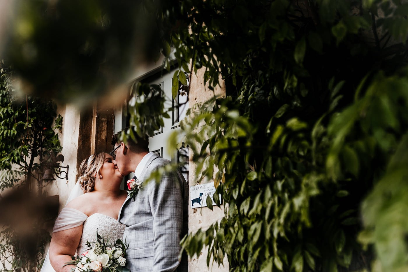 bride and groom kissing under the trees