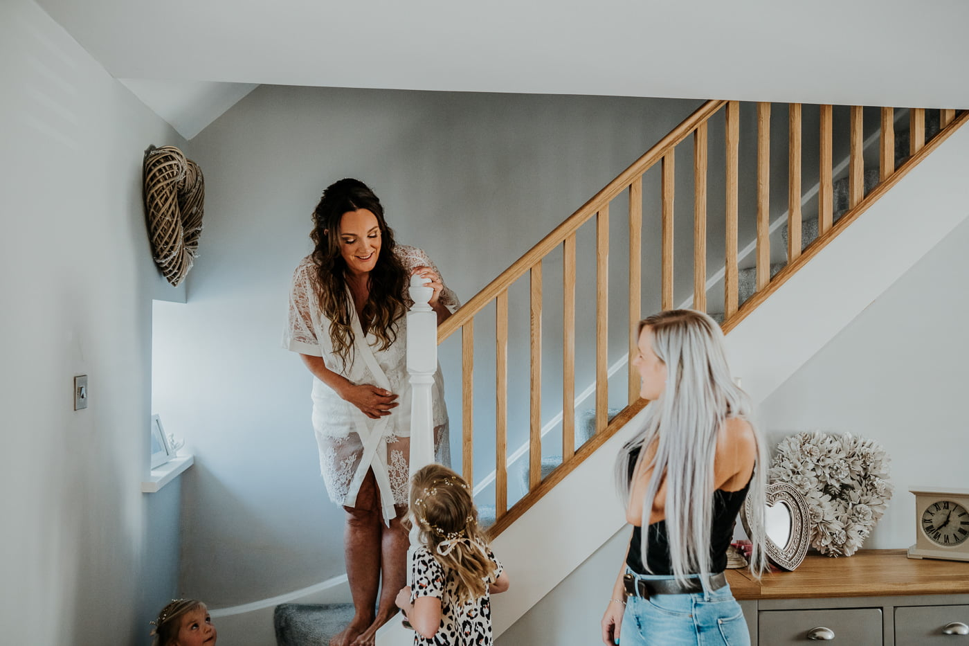 bride speaking to daughters on the stairs
