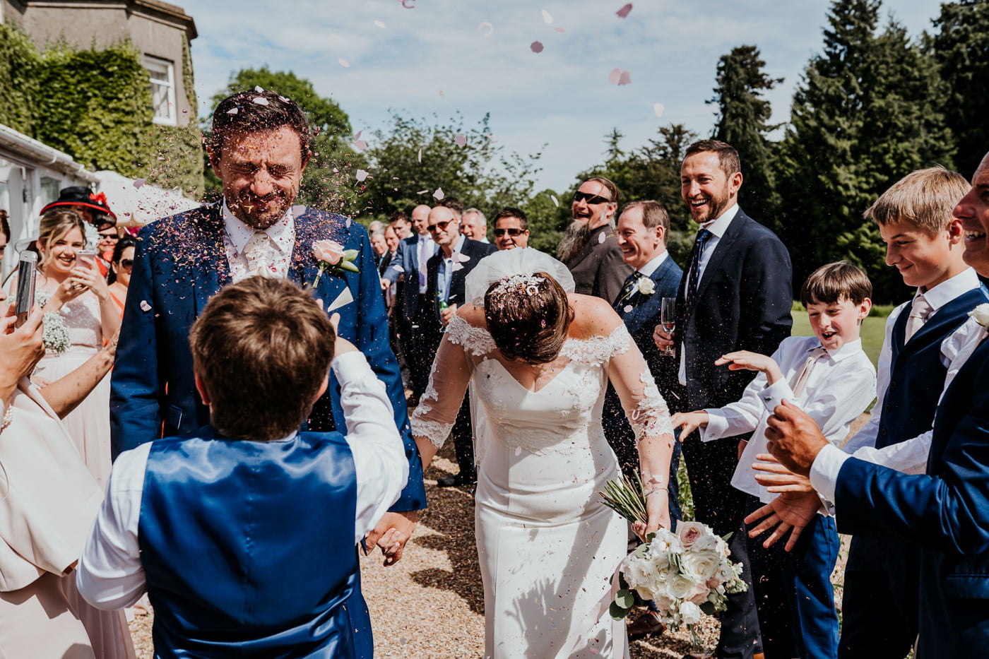 bride and groom getting confetti thrown in faces
