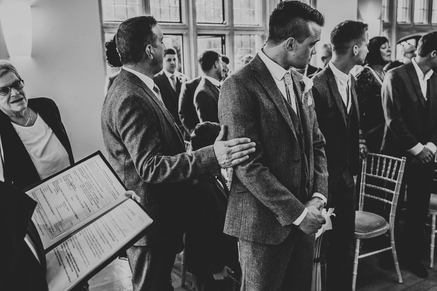 grooms dad comforting groom during wedding ceremony