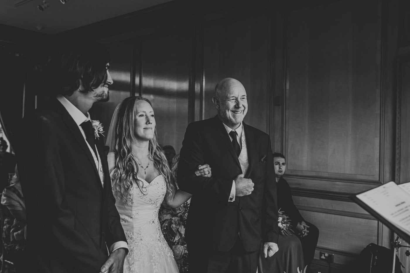 brides father smiling during wedding ceremony