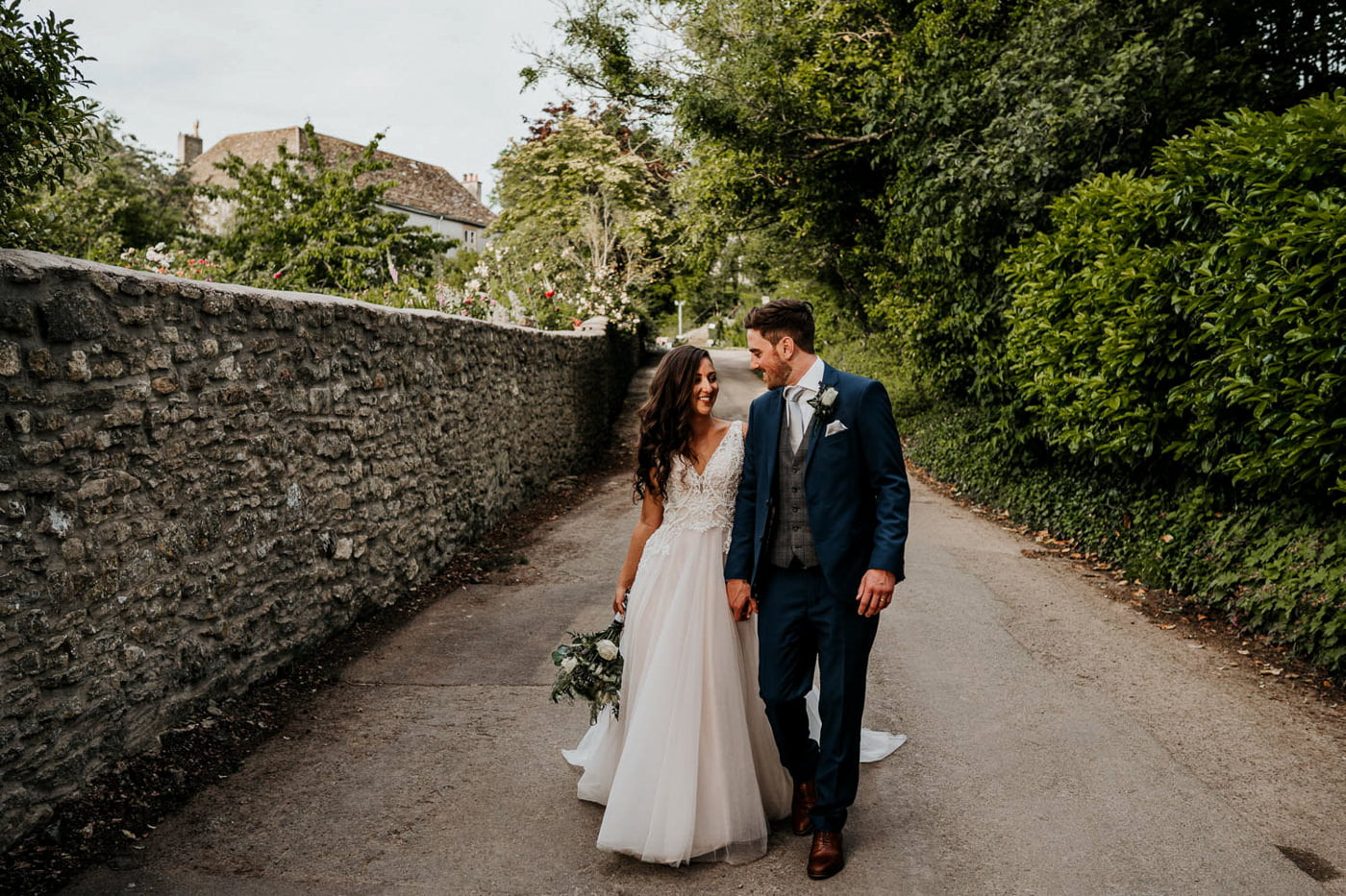 bride and groom walking through countryside village