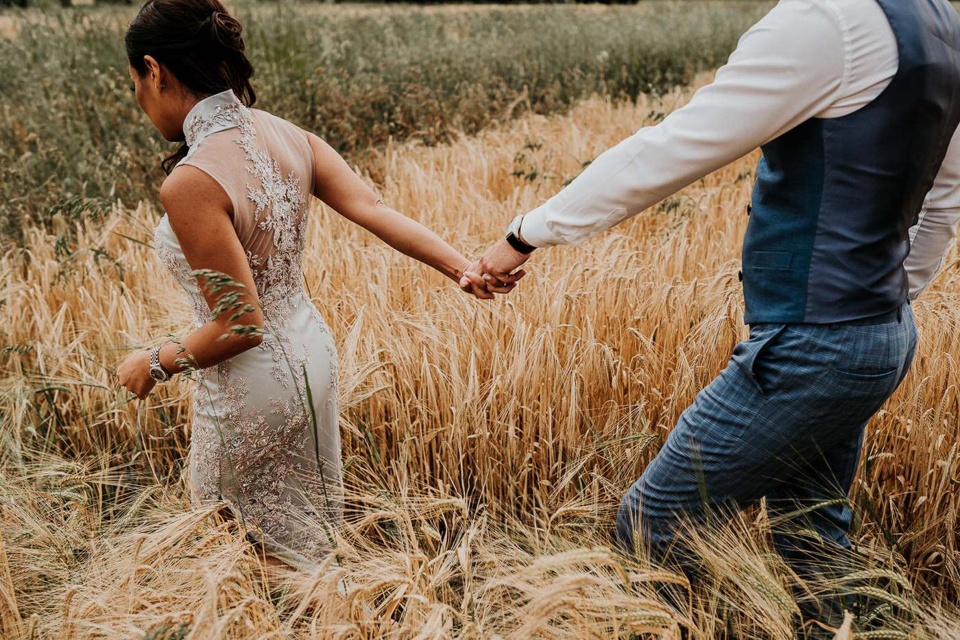 bride and groom walking through wheat field
