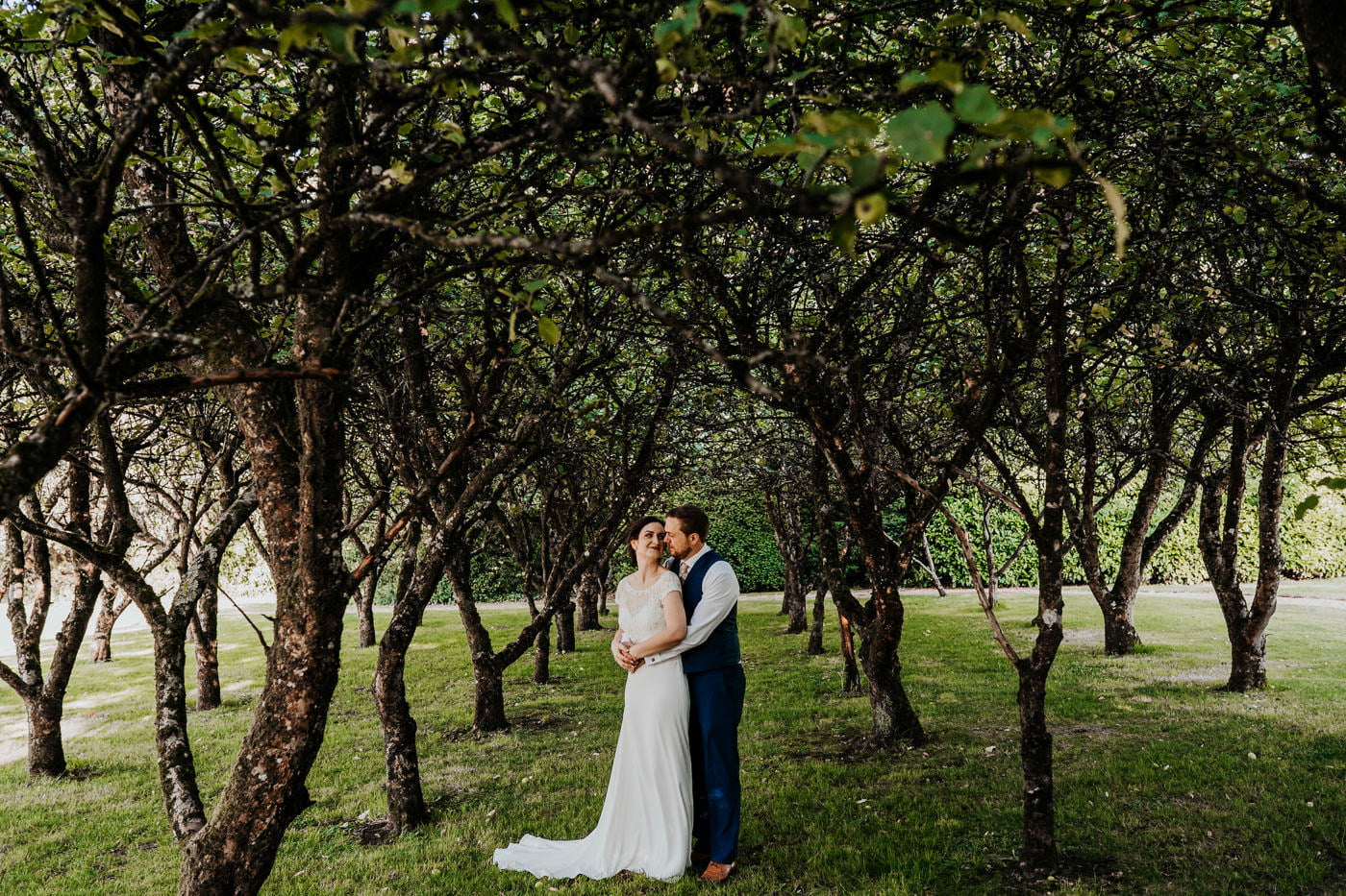 bride and groom stood under apple trees