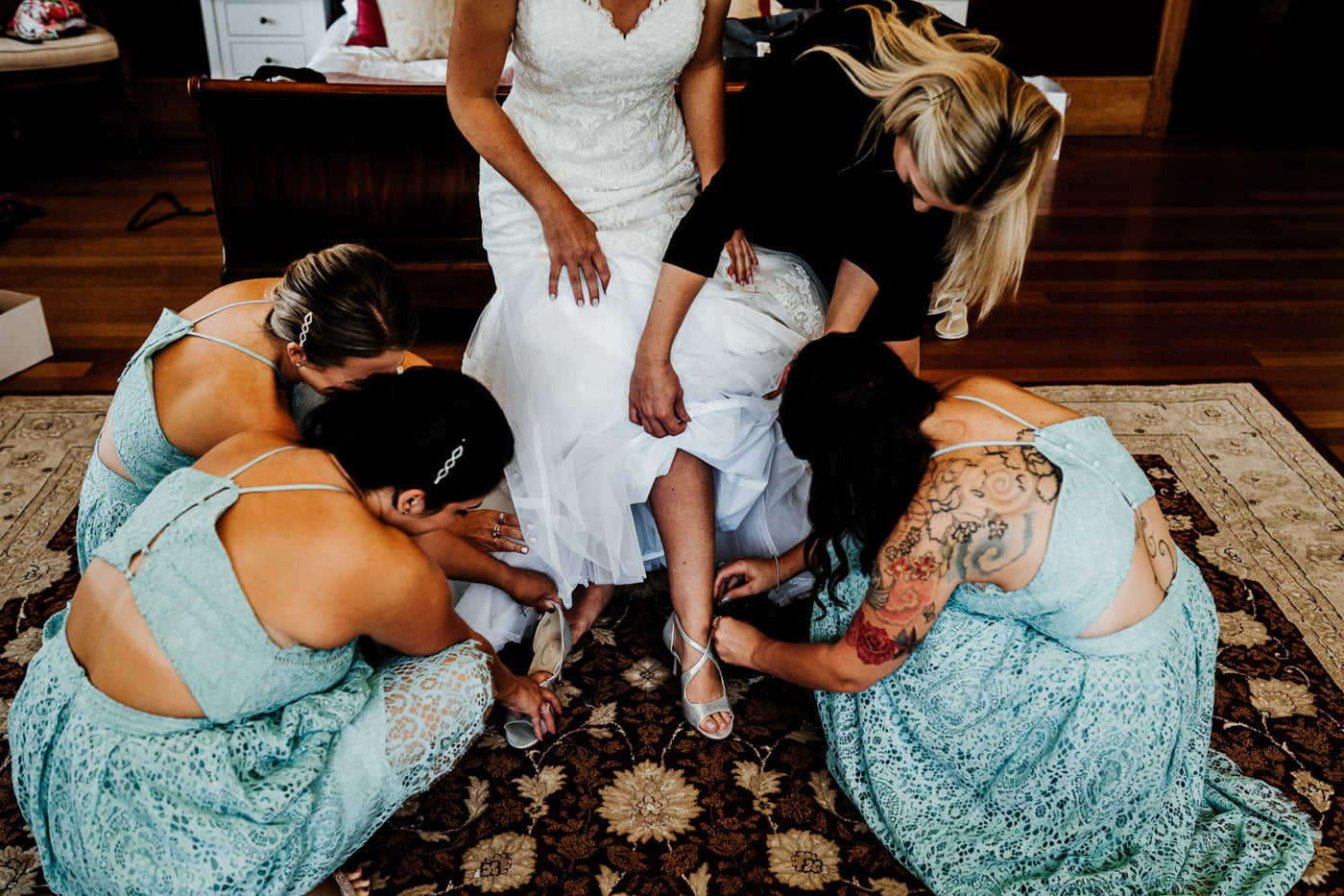 bridesmaids helping bride put her shoes on