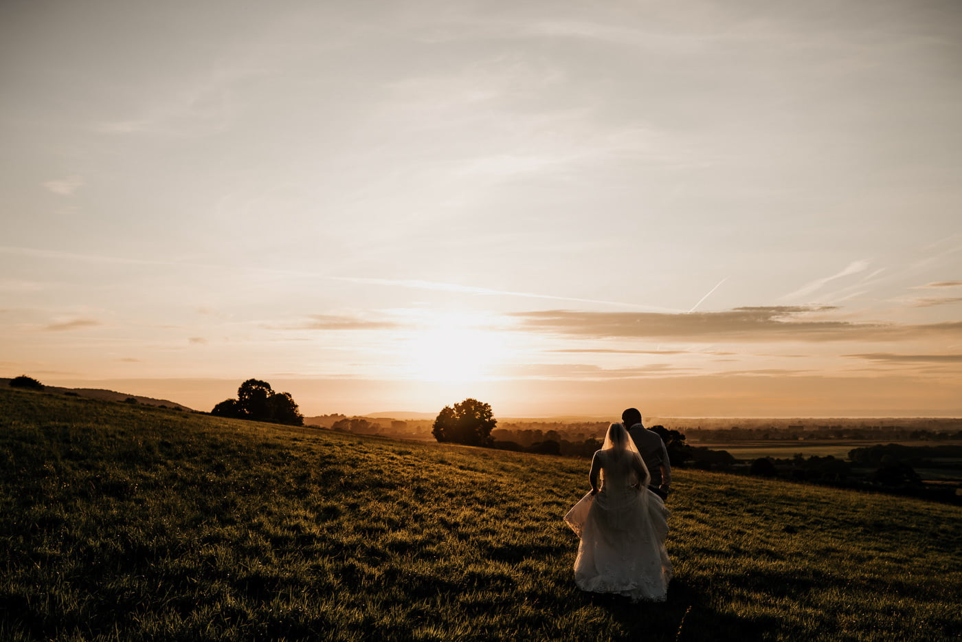 bride and groom walking through field during sunset