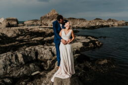bride and groom stood by tidal pool at tunnels beach