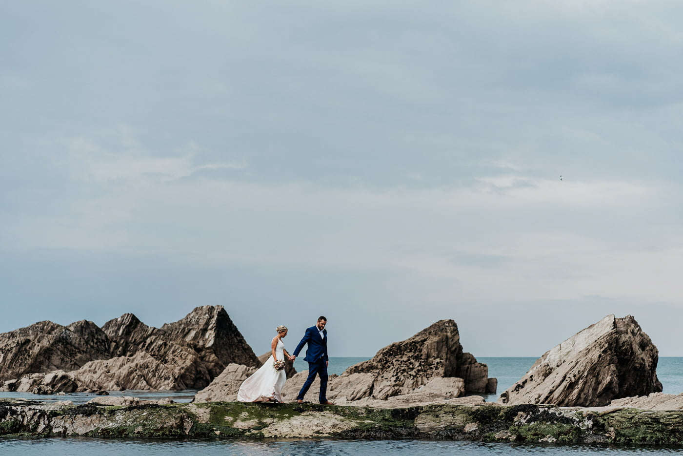 bride and groom walking along the sea