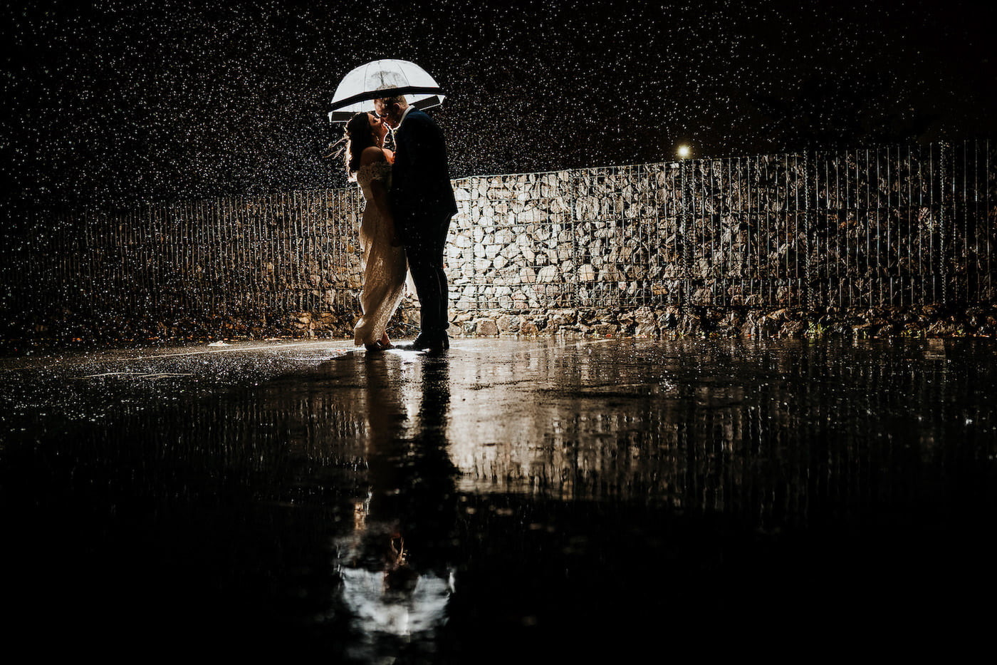 bride and groom stood in the rain in the dark