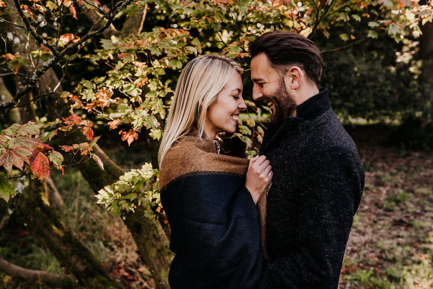 engaged couple getting cosy by the trees