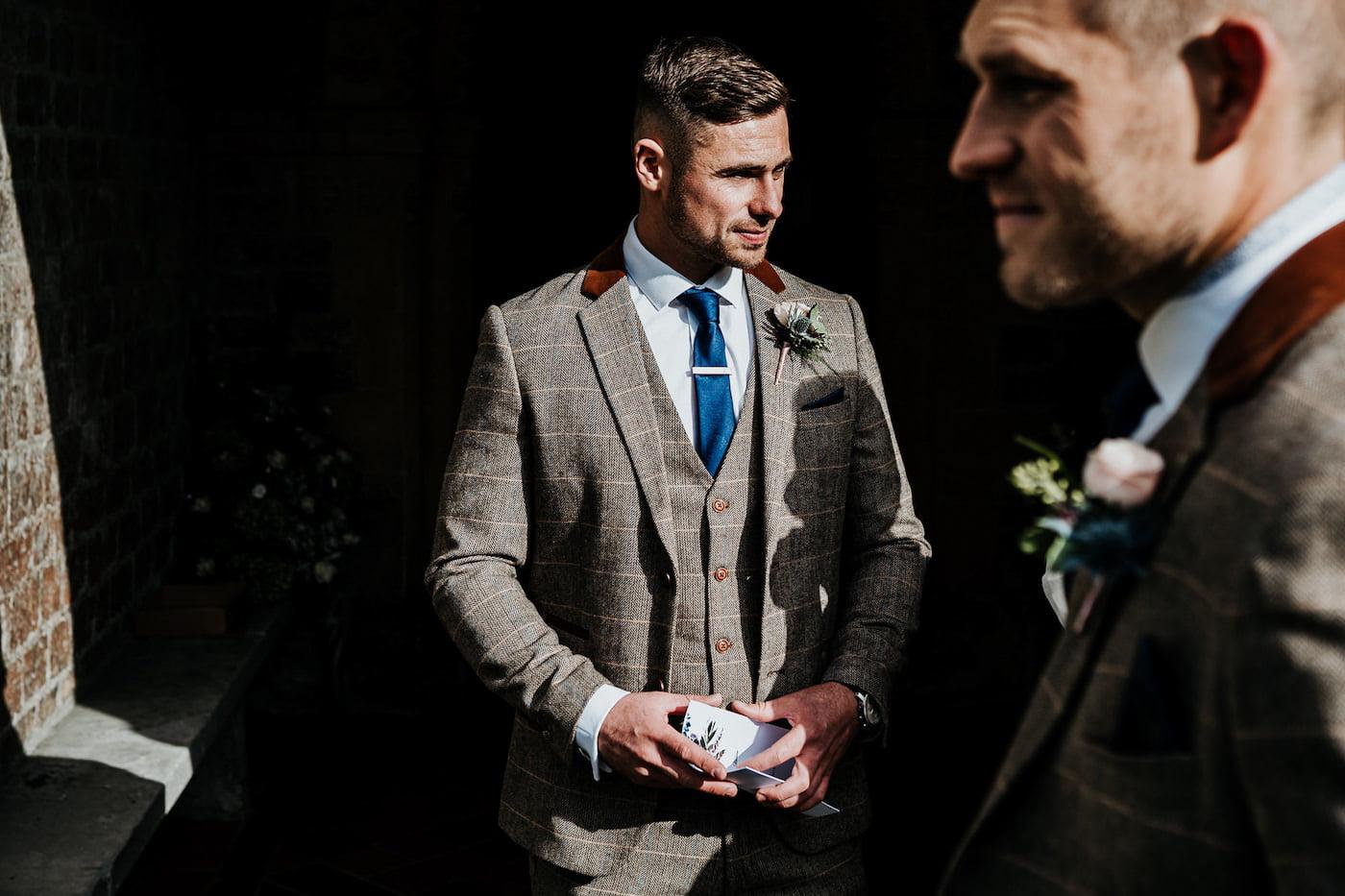 wedding groomsmen handing out stationary