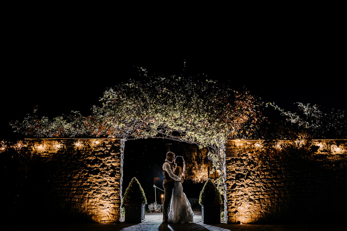 bride and groom stood by wall in the dark