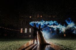 bride and groom holding smoke grenades