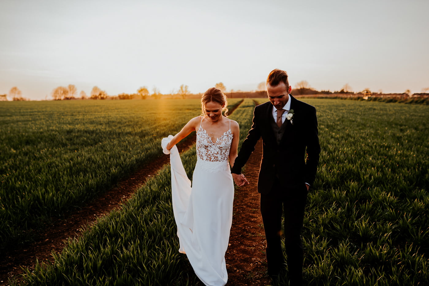 bride and groom walking through crop field