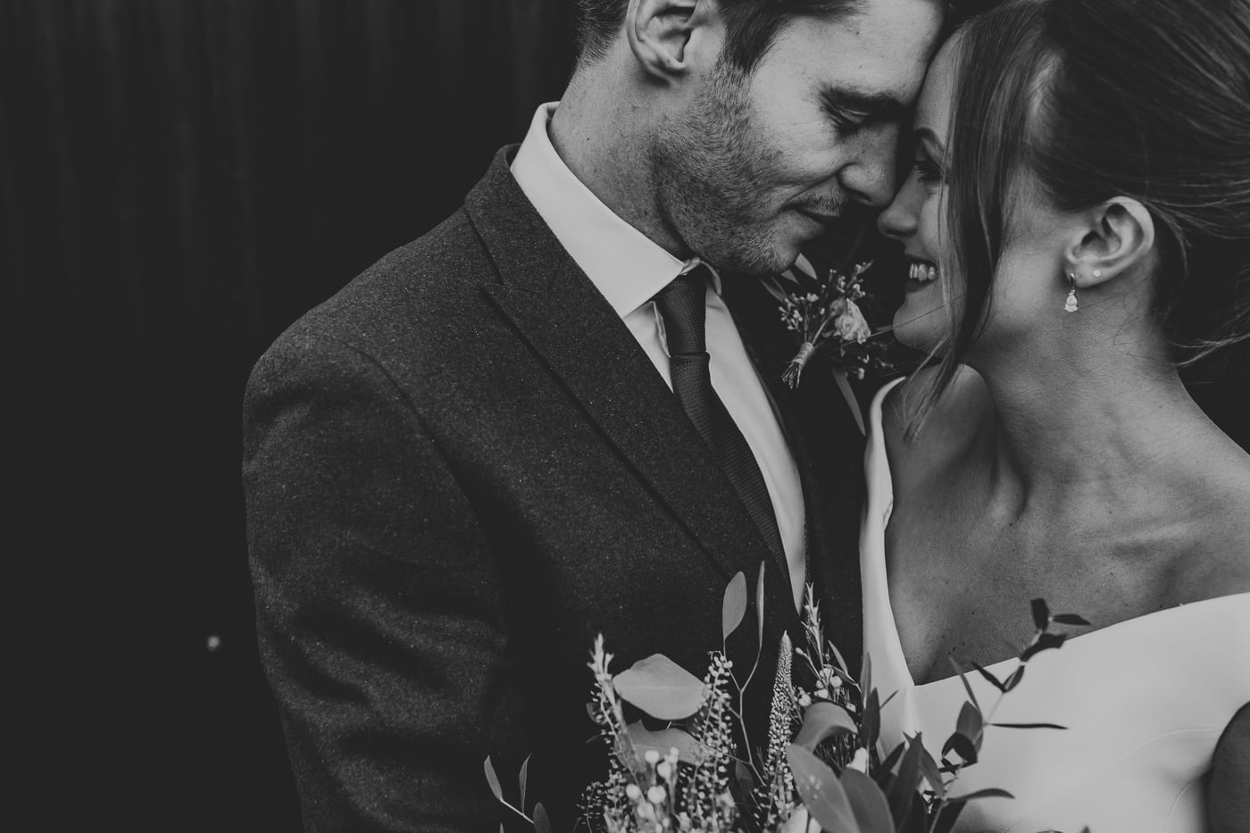 close up of bride and groom at stone barn